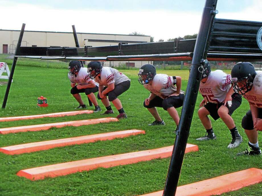 Torrington linemen get ready to take part in a drill this offseason. Photo: Peter Wallace — Register Citizen
