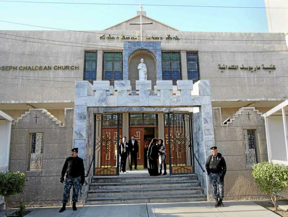 Iraqi police officers guard the entrance of St. Joseph's Chaldean Church before a Christmas mass in Baghdad, Iraq, Wednesday, Dec. 25, 2013. Militants on Wednesday launched two separate attacks against Christians in Baghdad, officials said. There was no immediate claim of responsibility for the attacks, but Iraq's dwindling Christian community, which is estimated to number about 400,000 to 600,000 people, has often been targeted by al-Qaida and other insurgents who see the Christians as unbelievers.(AP Photo/Karim Kadim) Photo: AP / AP