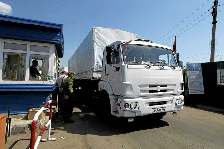 Ukrainian border guards look at the first truck as it passes the border post at Izvaryne, eastern Ukraine, Friday, Aug. 22, 2014. The first trucks in a Russian aid convoy crossed into eastern Ukraine on Friday, seemingly without Kiev's approval, after more than a week's delay amid suspicions the mission was being used as a cover for an invasion by Moscow. (AP Photo/Sergei Grits) Photo: AP / AP