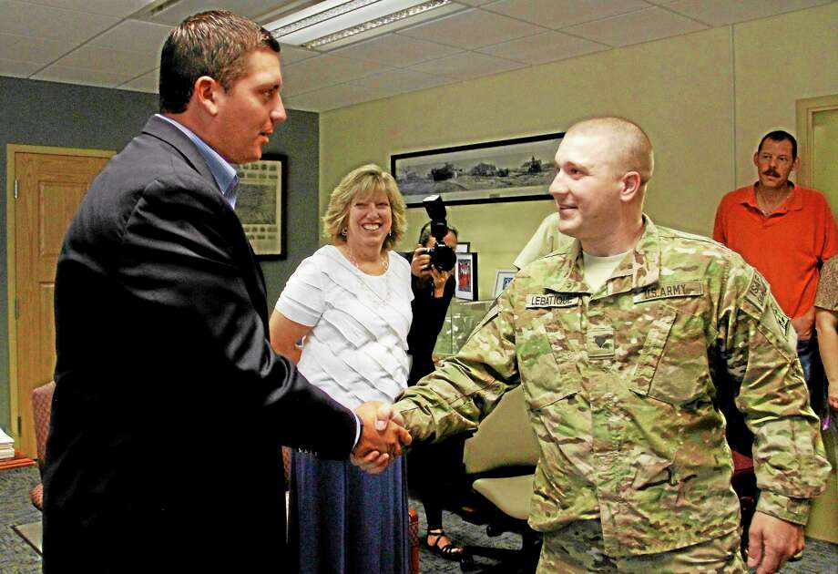 Mayor Ryan Bingham greets Spc. Brian Lebatique during a welcome reception for five Torrington guardsmen on Tuesday, Aug. 20, inside the mayor's office. Lebatique was one of five guardsmen invited to the reception after the quintet spent a year-long deployment in Afghanistan serving in the Air National Guard. Photo: Esteban L. Hernandez—Register Citizen