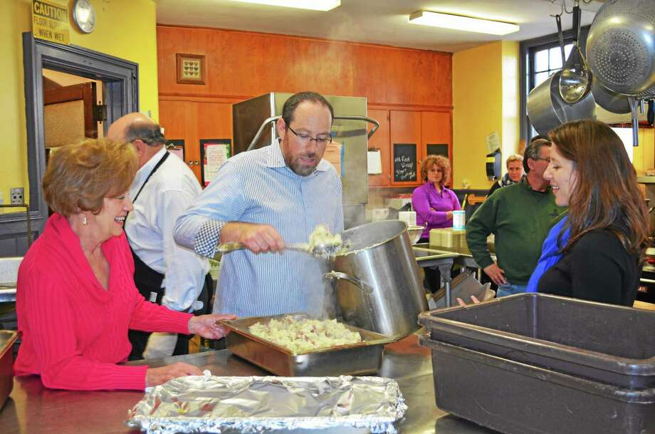 Richard Arum piles fresh made mashed potatoes into a pan to serve as part of Christmas dinner. The Arums, along with the Levines and Matisoffs, come together each Christmas to serve dinner to those in need at the Community Soup Kitchen on Prospect Street in Torrington. Photo: Kate Hartman — Register Citizen