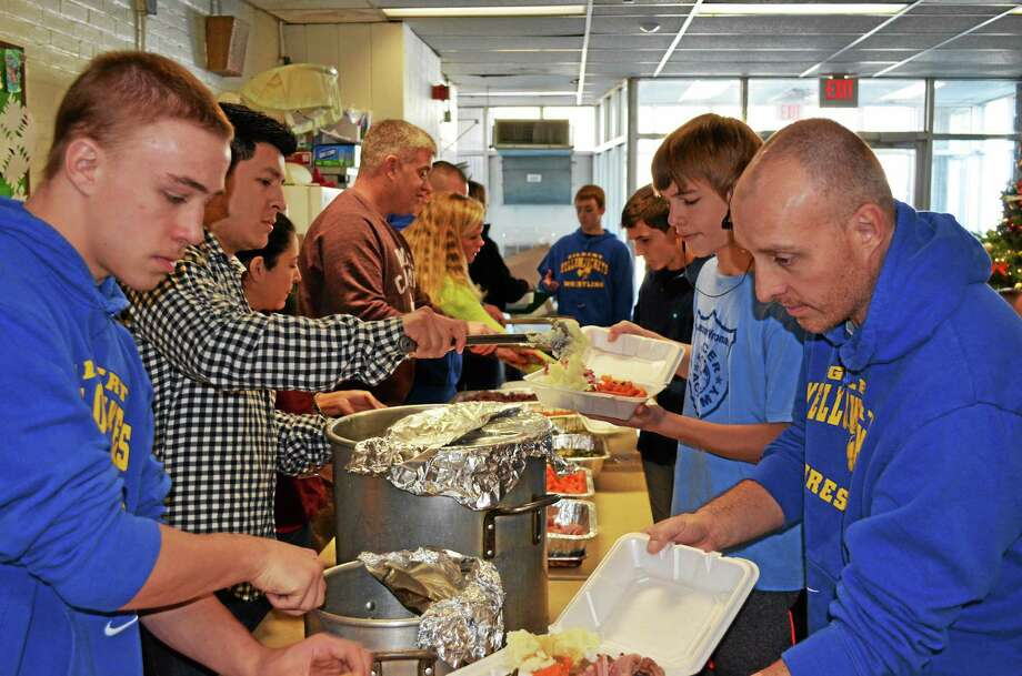 Members of the Gilbert School wrestling team served meals to the homeless at the Winsted YMCA on Christmas. Photo: Kate Hartman — Register Citizen