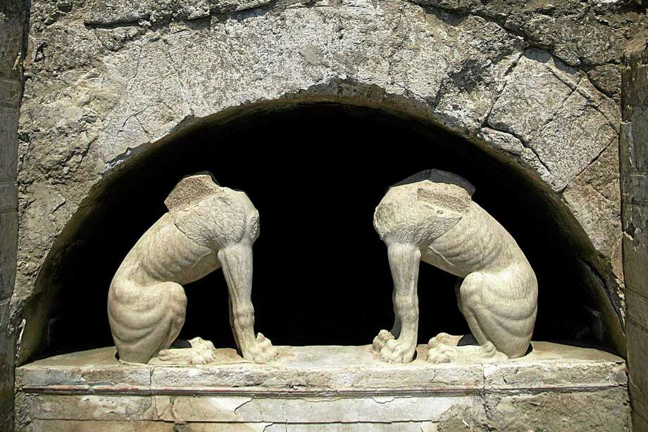 In this handout photo released by the Greek Culture Ministry on Thursday, Aug. 21, 2014, two large stone sphinxes are seen under a barrel-vault topping the entrance to an ancient tomb under excavation at Amphipolis in northern Greece. Archaeologists excavating the large grave mound on Thursday asked politicians and others seeking guided tours of the site to leave them in peace until the dig is completed. The partially uncovered tomb, from the end of Greek warrior-king Alexander the Greatís reign, has captivated the public imagination, fueling wild speculation that it may contain rich treasure and the bones of an ancient celebrity. (AP Photo/Culture Ministry, HO) Photo: AP / Greek Culture Ministry