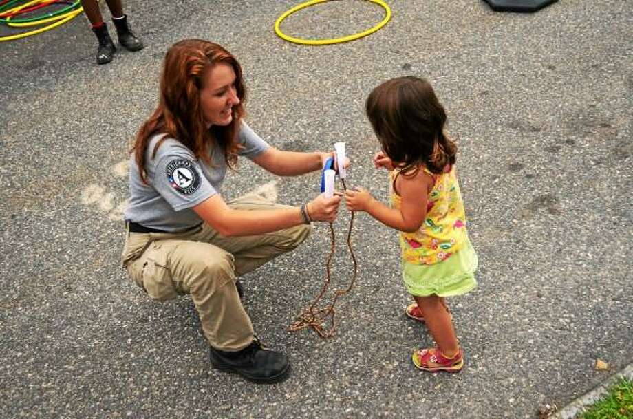 Sarah Kolb with Americorps hands a jump rope to Isabella Alciati, 3, of Torrington, during a recent Main Street Marketplace demonstration on fitness. (John Berry - Register Citizen)
