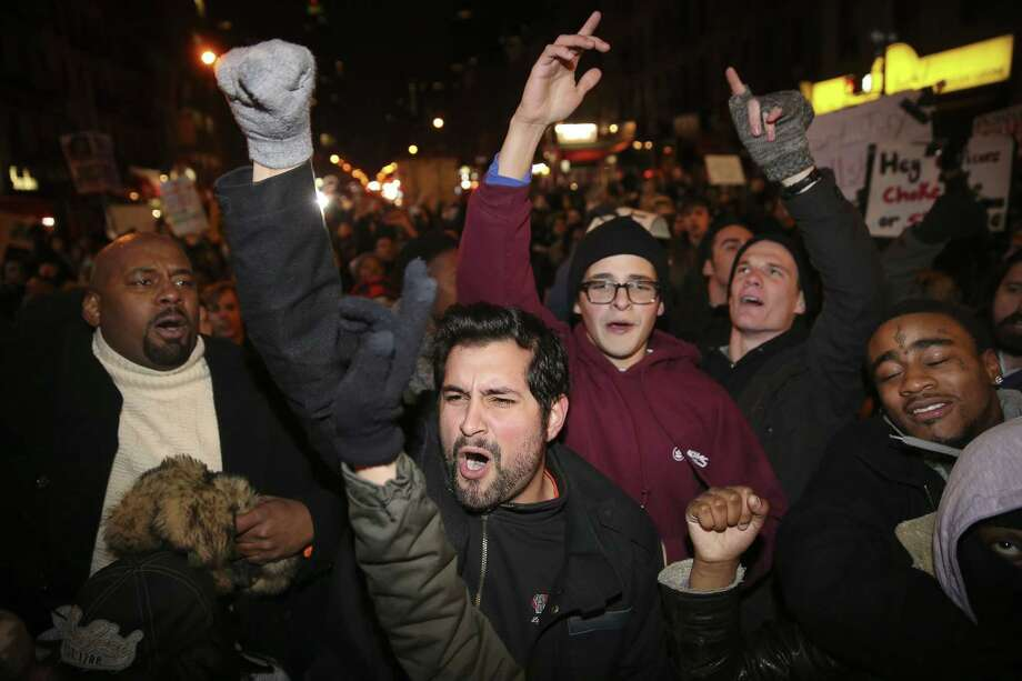 Protestors march against a grand jury's decision not to indict the police officer involved in the death of Eric Garner, Thursday, Dec. 4, 2014, in New York. A grand jury cleared a white New York City police officer Wednesday in the videotaped chokehold death of Garner, an unarmed black man, who had been stopped on suspicion of selling loose, untaxed cigarettes, a lawyer for the victim's family said. (AP Photo/John Minchillo) Photo: AP / FR170537 AP