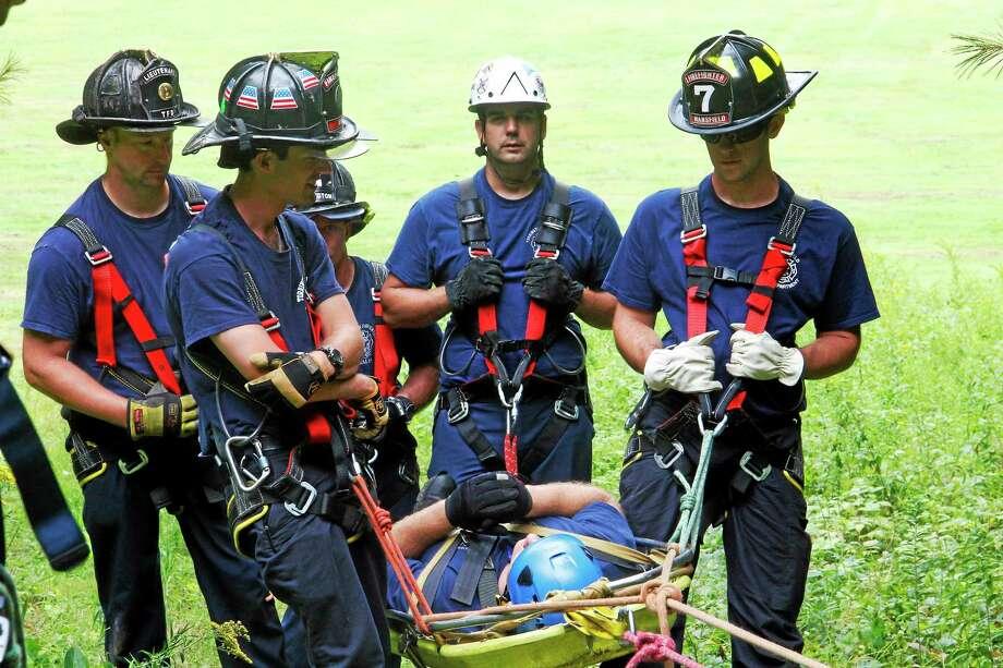 "Firefighters participating in a drill carry a ""victim"", Alex Battaglino, a Torrington Fire Department firefighter, up a hill at Major Besse Park on Thursday, Aug. 21, in Torrington. Photo: Esteban L. Hernandez — Register Citizen"