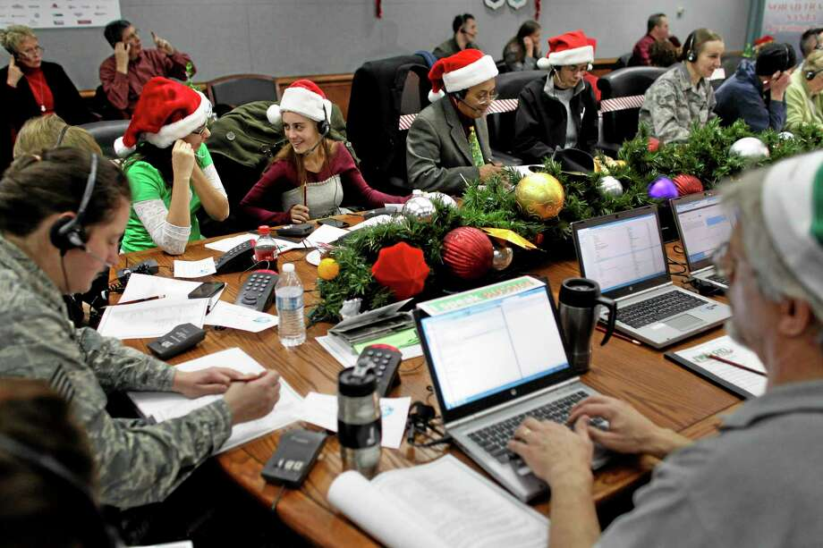 FILE - In this Dec. 24, 2012 file photo, Lizzie Solano, center, and her sister Sarah take phone calls from children asking where Santa is and when he will deliver presents to their house, during the annual NORAD Tracks Santa Operation, at the North American Aerospace Defense Command, or NORAD, at Peterson Air Force Base, in Colorado Springs, Colo. The U.S. and Canadian military will entertain millions of kids again this Christmas Eve with second-by-second updates on Santaís global whereabouts. But thereís something new this year: public criticism.  A children's advocacy group says an animated video on the NORAD Tracks Santa website injects militarism into Christmas by showing fighter jets escorting Santa's sleigh. (AP Photo/Brennan Linsley, File) Photo: AP / AP