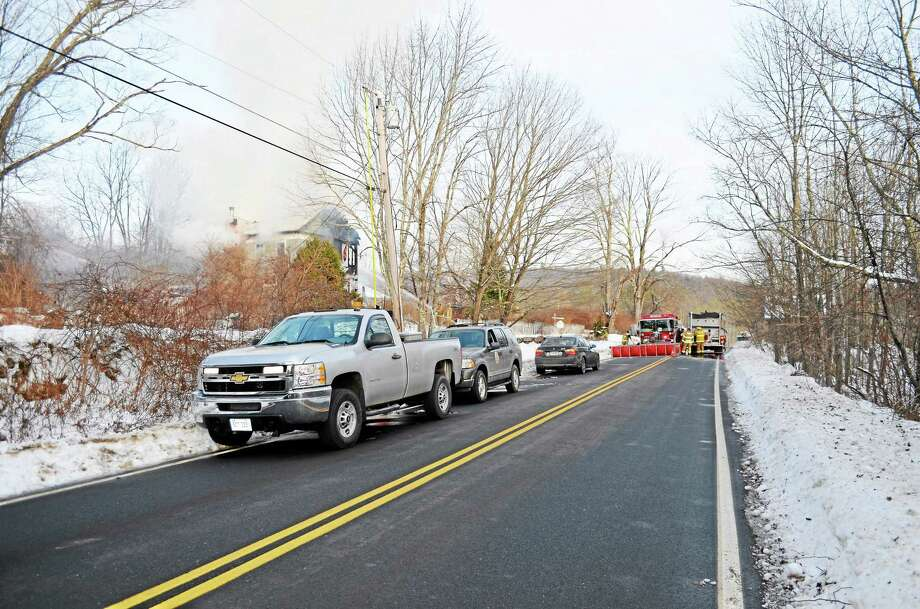 Crews work to battle a fire at the Sugar Shack Farm, near the intersection of Ashley Road and Blue Street, in Winchester on Dec. 19. Photo: Kate Hartman—Register Citizen