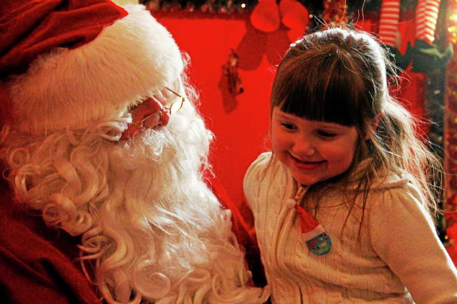 Elizabeth Pronovost, 4, of Watertown, smiles as she tells Santa Claus what she would like for Christmas inside his house at Carl Bozenski's Christmas Village. Photo: Esteban L. Hernandez—Register Citizen
