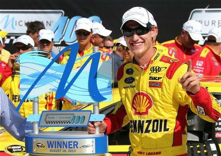 Joey Logano celebrates after winning the NASCAR Sprint Cup series Pure Michigan 400 auto race at Michigan International Speedway in Brooklyn, Mich., Sunday, Aug. 18, 2013. (AP Photo/Bob Brodbeck) Photo: AP / FR3471 AP
