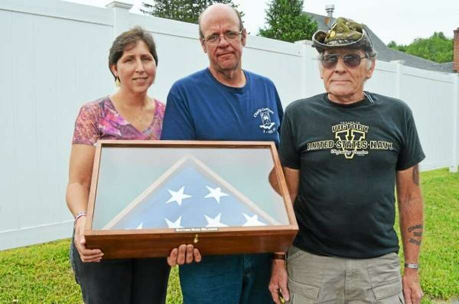 Tracy and Marc Melanson hold the flag that was presented to them by Art Melycher, right. (Mercy Quaye-Register Citizen)