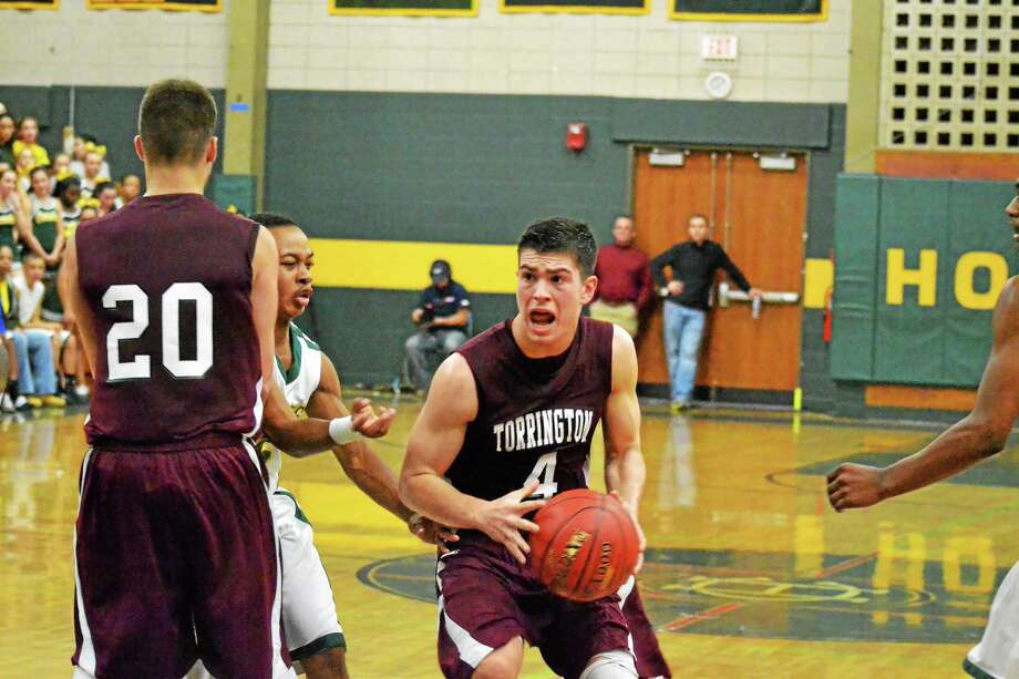 Torrington's John McCarthy drives through traffic during the Red Raiders 69-55 win over Holy Cross. McCarthy scored a game high 24 points. Photo: Pete Paguaga — Register Citizen