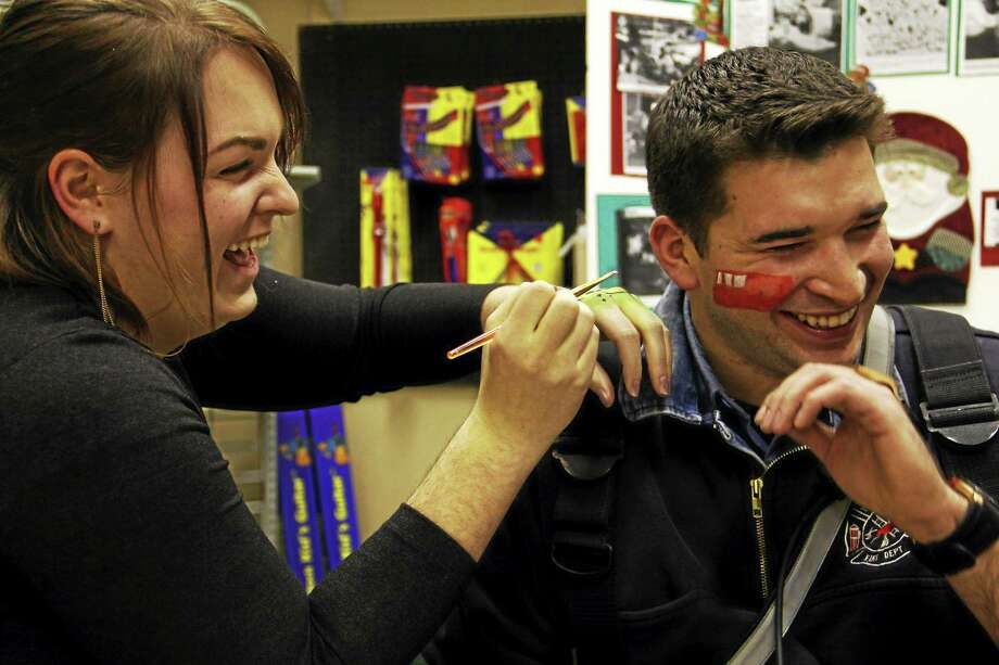 Torrington firefighter Jordan Tyrell laughs as face painter Emily Metta Starr paints a firetruck on his cheek on Friday, Dec. 5, during the Christmas Village Toy Shower in Torrington. Esteban L. Hernandez Register Citizen Photo: Photos By Esteban L. Hernandez — Register Citizen