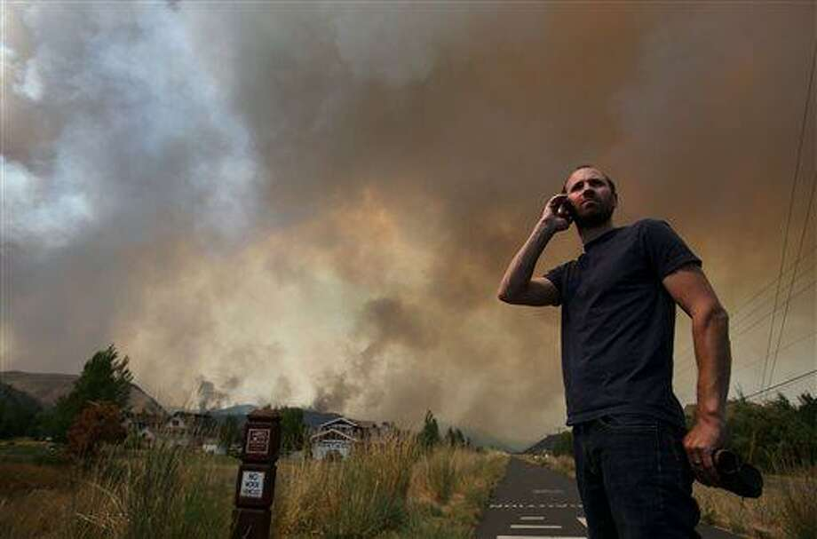 Kevin Bullock, of Bellevue, Idaho, watches smoke from the 64,000 acre Beaver Creek Fire on Friday, Aug., 16, 2013 north of Hailey, Idaho. A number of residential neighborhoods have been evacuated because of the blaze.(AP Photo/Times-News, Ashley Smith) MANDATORY CREDIT Photo: AP / The Times-News
