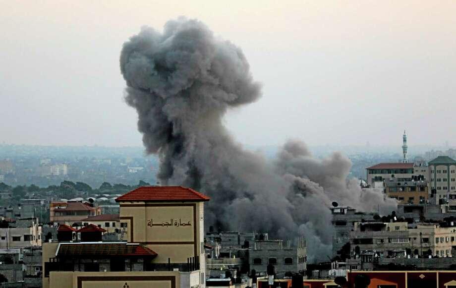 Smoke and dust rise after an Israeli strike hit Gaza City in the northern Gaza Strip, Wednesday, Aug. 20, 2014. (AP Photo/Adel Hana) Photo: AP / AP