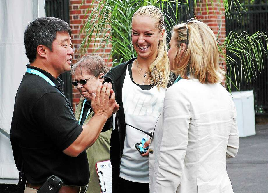 Peter Casolino — RegisterWTA Tour supervisor Tony Cho high-fives tennis pro Sabine Lisicki along with Ann Worcester before the Draw ceremony at the New Haven Open at Yale.pcasolino@newhavenregister.com Photo: Journal Register Co.