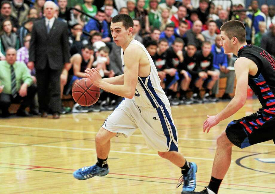 Lewis Mills' Nate Cook drives to the lane in the Spartans 55-45 win. Cook scored 18 points in the win. Photo: Marianne Killackey — Special To Register Citizen  / 2013