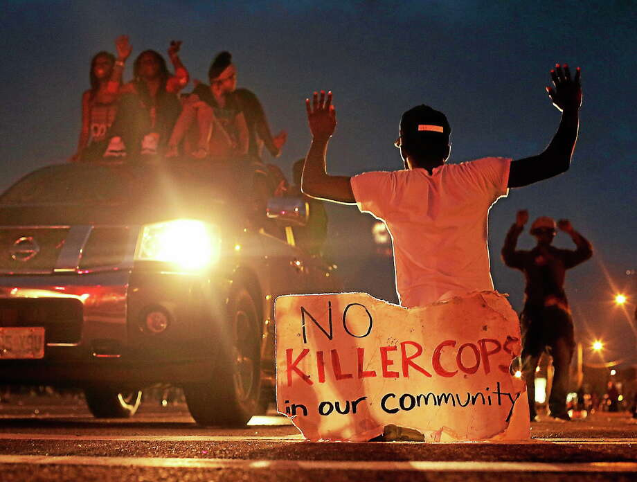 People protest Aug. 17, 2014, for Michael Brown, who was killed by a police officer last Saturday in Ferguson, Mo. Photo: AP Photo/Charlie Riedel  / AP