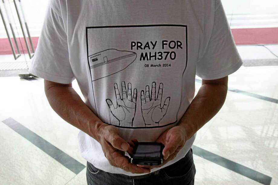 """A man wearing a T-shirt printing with """"Pray for MH370"""" stands with a smartphone at a hotel in Putrajaya, Malaysia, Saturday, March 15, 2014. The Malaysian jetliner missing for more than a week had its communications deliberately disabled and its last signal came about 7 1/2 hours after takeoff, meaning it could have ended up as far as Kazakhstan or into the southern reaches of the Indian Ocean, Malaysian Prime Minister Najib Razak said Saturday. (AP Photo/Lai Seng Sin) Photo: AP / AP"""