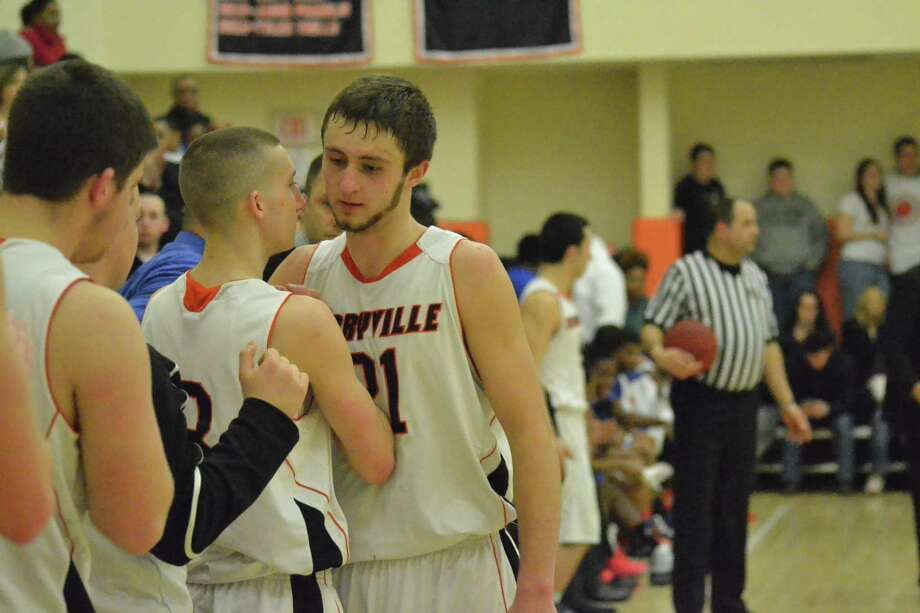 Terryvilleís Tyler Trillo (left) hugs teammates Jacob Johnson (right) after he is taken out of the game for the final time. Photo: Pete Paguaga — Register Citizen