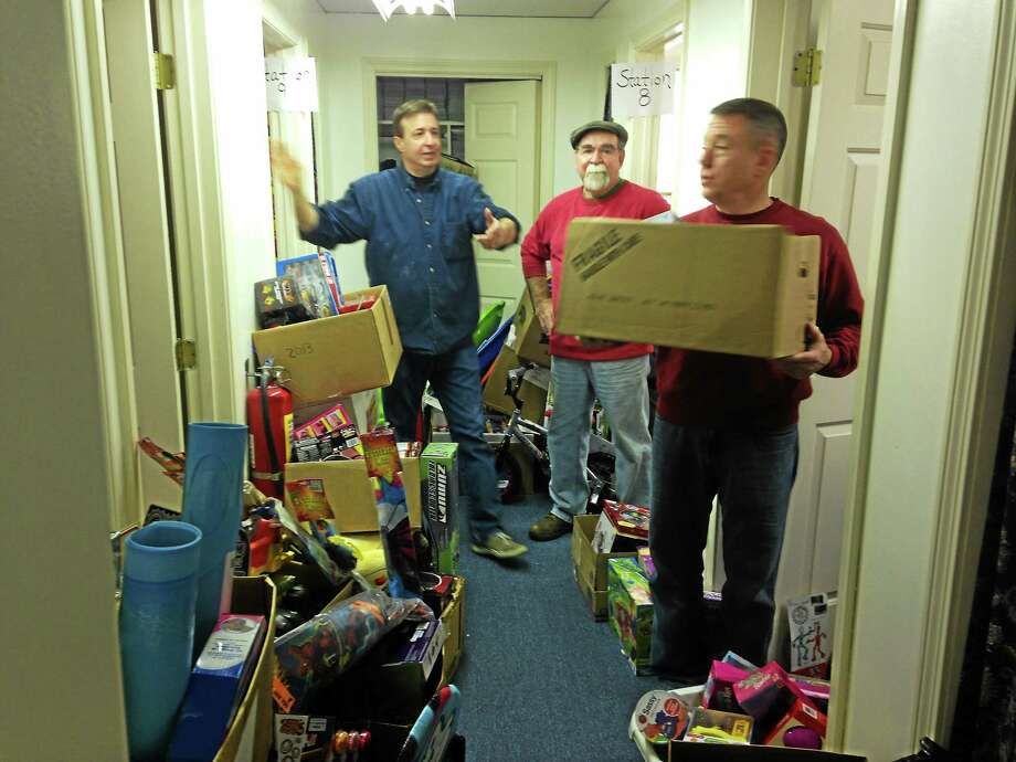 """Elves"" from Friendly Hands Food Bank organize gifts to give to local families in the Torrington area. Photo: Mercy Quaye — Register Citizen"