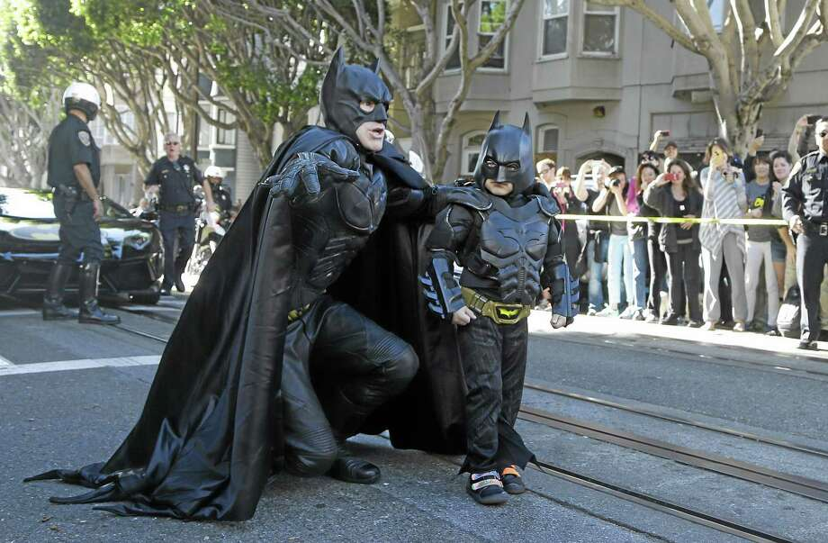 """Miles Scott, dressed as Batkid, right, walks with Batman before saving a damsel in distress in San Francisco, Friday, Nov. 15, 2013.  San Francisco turned into Gotham City on Friday, as city officials helped fulfill Scott's wish to be """"Batkid.""""†Scott, a leukemia patient from Tulelake in far Northern California, was called into service on Friday morning by San Francisco Police Chief Greg Suhr to help fight crime, The Greater Bay Area Make-A-Wish Foundation says. (AP Photo/Jeff Chiu) Photo: AP / AP"""