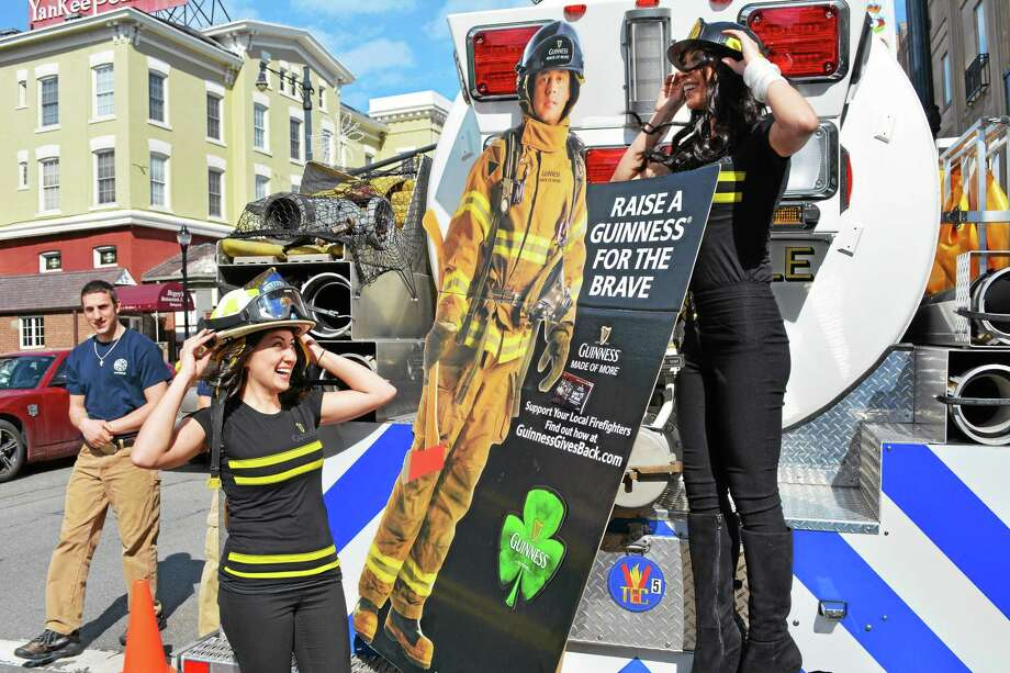 Marguerite Mahon and Monica Larue, who were on hand to support the Guinness Gives Back campaign and the Leary Firefighters Foundation, try on some gear on the back of a Drakeville Volunteer Fire Department tanker truck outside a benefit for the department at Backstage in Torrington Saturday. Photo: Esteban L. Hernandez — Register Citizen