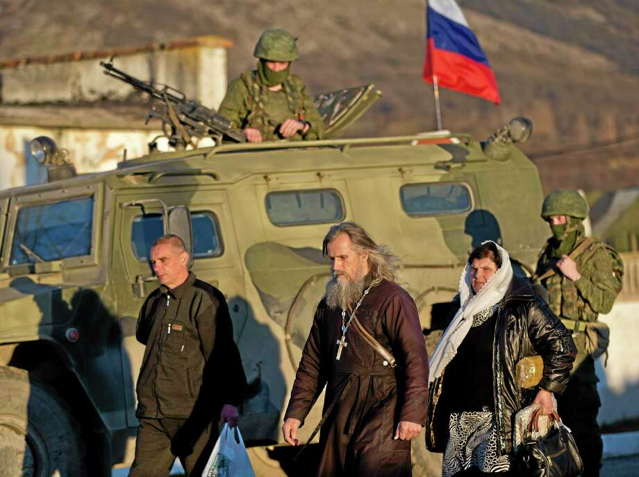 Archbishop Clement of Ukrainian Orthodox church, center, walks past a pro-Russian armored vehicle and soldiers  outside an Ukrainian military base in Perevalne, Ukraine, Saturday, March 15, 2014. Tensions are high in the Black Sea peninsula of Crimea, where a referendum is to be held Sunday on whether to split off from Ukraine and seek annexation by Russia.(AP Photo/Vadim Ghirda) Photo: AP / AP