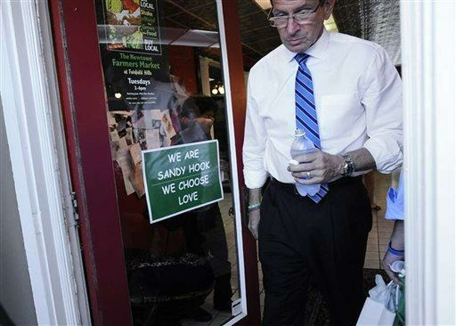 Connecticut Gov. Dannel P. Malloy tours the downtown business district of Sandy Hook in Newtown, Conn., Wednesday, July 31, 2013.  Malloy is visiting to meet with business owners and talk about economic recovery after the December elementary school shooting that killed 20 students and six adults. (AP Photo/Jessica Hill) Photo: AP / FR125654 AP