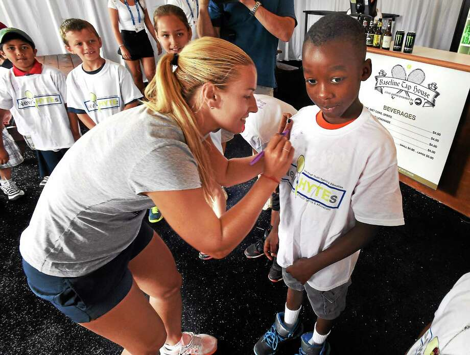 Dominika Cibulkova, the fifth seed at the Connecticut Open, signs the T-shirt of Martin Duff of New Haven, 9, a member of New Haven Youth Tennis & Education, or New HYTEs, after the draw ceremony. Cibulkova will face Andrea Petkovic in the first round. Photo: Mara Lavitt — Register  / Mara Lavitt