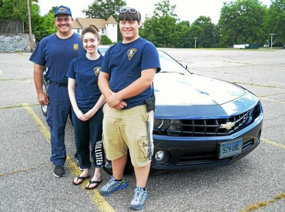 From left: Officer Steven Cloutier, Caitlin Cloutier and Chris Beyus stand in front of Steve Cloutier's 2011 Chevy Camaro on Wednesday, August 14. All three serve in the Torrington Police Explorer's program, which is hosting a car show on Friday on Main Street.