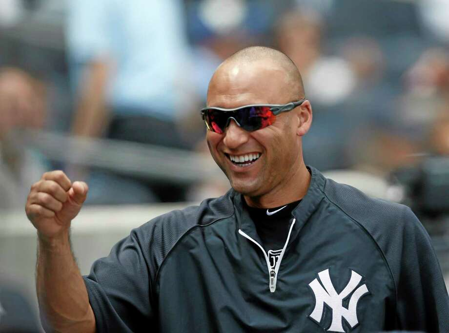 New York Yankees Derek Jeter, sitting out a game, greets teammates in the dugout during a game at Yankee Stadium on Aug. 7. Photo: Kathy Willens — The Associated Press  / AP