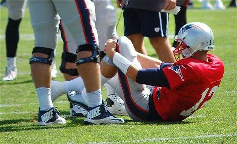 New England Patriots quarterback Tom Brady  grabs his left knee after an apparent injury during a joint workout with the Tampa Bay Buccaneers at NFL football training camp, in Foxborough, Mass., Wednesday, Aug. 14, 2013. (AP Photo/Will DiTullio) Photo: AP / AP