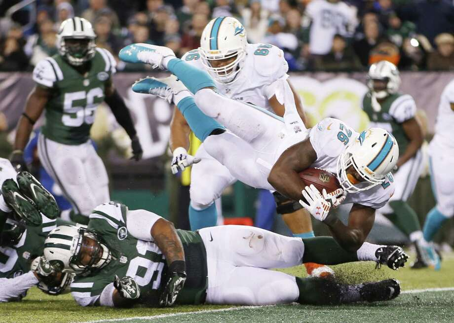 Dolphins running back Lamar Miller (26) leaps over Jets defensive end Sheldon Richardson (91) for a touchdown during the fourth quarter Monday. Photo: Kathy Willens — The Associated Press  / AP