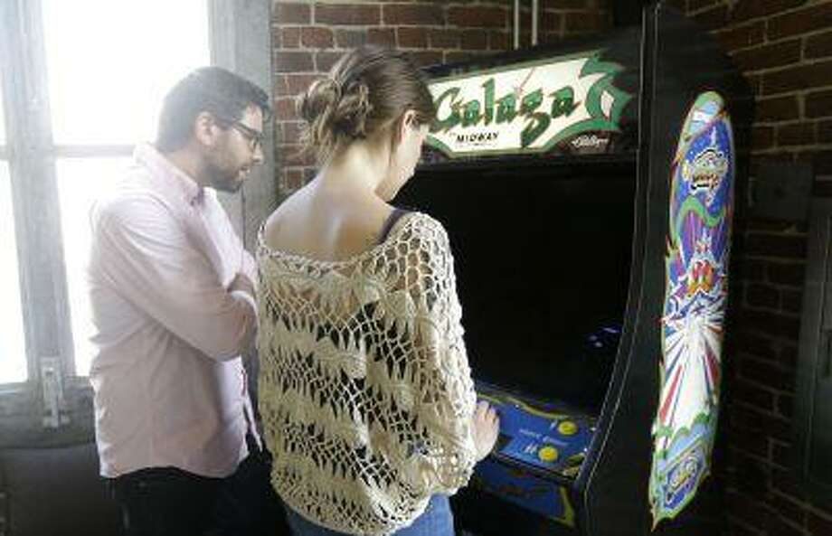 John Korn, left, watches as Amanda Day plays a Galaga arcade game which was delivered by All You Can Arcade at the Eleven Inc office in San Francisco, Tuesday, July 30, 2013. Photo: AP / AP
