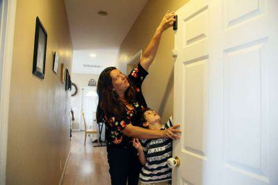 """Jo Ashline sets a door lock, accompanied by her son, Andrew, 11, who has autism, at their home in Orange, Calif. on Friday, Aug. 9, 2013. Ashline says, """"We take steps at home, locks on every door, gates, alarms but there's always, in the forefront of our minds, the thought that one tiny mistake could prove fatal."""" The phenomenon goes by various names - wandering, elopement, bolting - and about half of autistic children are prone to it, according to research published in 2012 in the journal Pediatrics. It has claimed the lives of more than 60 children in the past four years and can make daily life a harrowing, never-let-your-guard-down challenge for parents whose sons and daughters are at risk. Photo: AP / AP"""