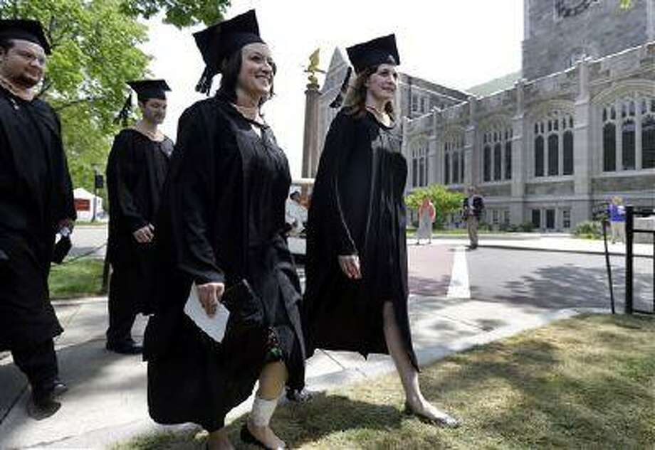 Liza Cherney, left, and Brittany Loring, right, lead the procession of graduates of the Carroll School of Management during commencement ceremonies at Boston College in Boston, Monday, May 20, 2013. The two women were injured in the Boston Marathon bombings on April 15, with Loring needing three operations after her left leg was struck by shrapnel from the first of the twin blasts. Cherney was standing next to her close friend and classmate Loring and was also badly hurt. (AP Photo/Elise Amendola) Photo: AP / AP