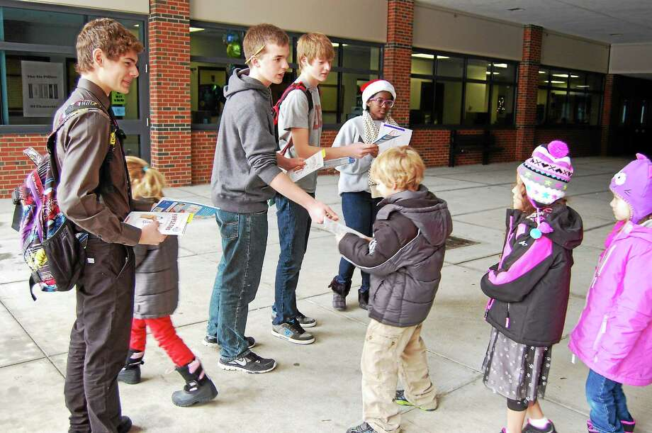 High school students from the Gilbert School hand out books to fourth-graders as part of an effort to increase literacy Friday. Photo: Mercy Quaye—Register Citizen