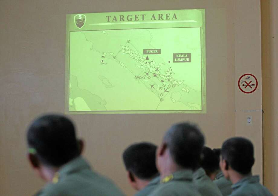 """Indonesian Air Force personnel of the 5th Air Squadron """"Black Mermaids"""" listen to a briefing as an operation map is projected on the wall following a search mission for the missing Malaysia Airlines Boeing 777 that was conducted over the Strait of Malacca, at Suwondo air base in Medan, North Sumatra, Indonesia, Friday, March 14, 2014. The jetliner vanished nearly a week ago with 239 people aboard. (AP Photo/Binsar Bakkara) Photo: AP / AP"""