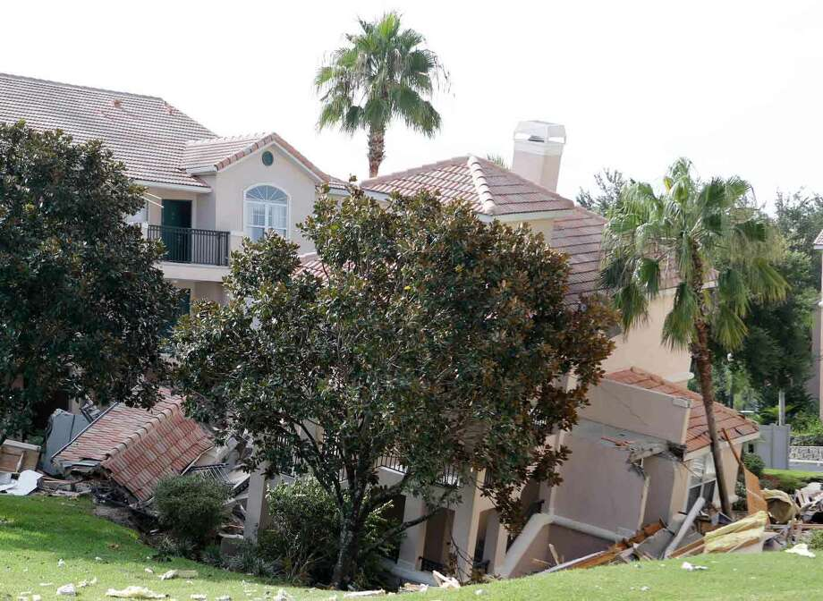 A portion of a building rests in a sinkhole Monday, Aug. 12, 2013 in Clermont, Fla. The sinkhole, 40 to 50 feet in diameter, opened up overnight and damaged three buildings at the Summer Bay Resort.  (AP Photo/John Raoux) Photo: ASSOCIATED PRESS / AP2013