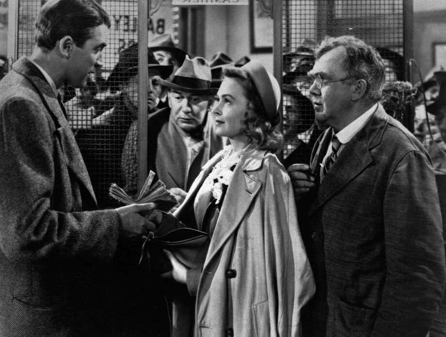 """In this undated file photo James Stewart, left, Thomas Mitchell, right, and Donna Reed appear in a scene from the 1946 film """"It's A Wonderful Life."""" Folks in Seneca Falls, N.Y., think Bailey's make-believe hometown, Bedford Falls in the movie, was heavily inspired by their quaint upstate town. This cannot be proven, and director Frank Capra never confirmed such a connection, but that hasn't stopped locals in Seneca Falls from celebrating the beloved movie every December. (AP Photo, File) Photo: AP / AP"""