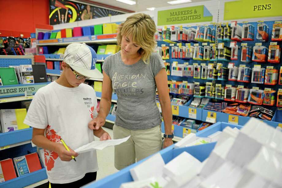 In this July 30 photo, Jill Courtney, right, shops for school supplies for her sons, Will, left, and Reid, not seen, at a Target store in St. Joseph, Missouri. Photo: St. Joseph News-Press, Sait Serkan Gurbuz — The Associated Press  / St. Joseph News-Press