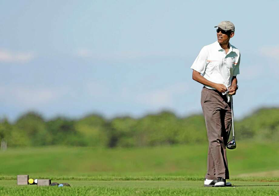 President Barack Obama prepares to tee off while golfing at Vineyard Golf Club, in Edgartown, Mass., on the island of Martha's Vineyard, Thursday, Aug. 14, 2014. President Obama is taking a two-week summer vacation on the island. (AP Photo/Steven Senne) Photo: AP / AP