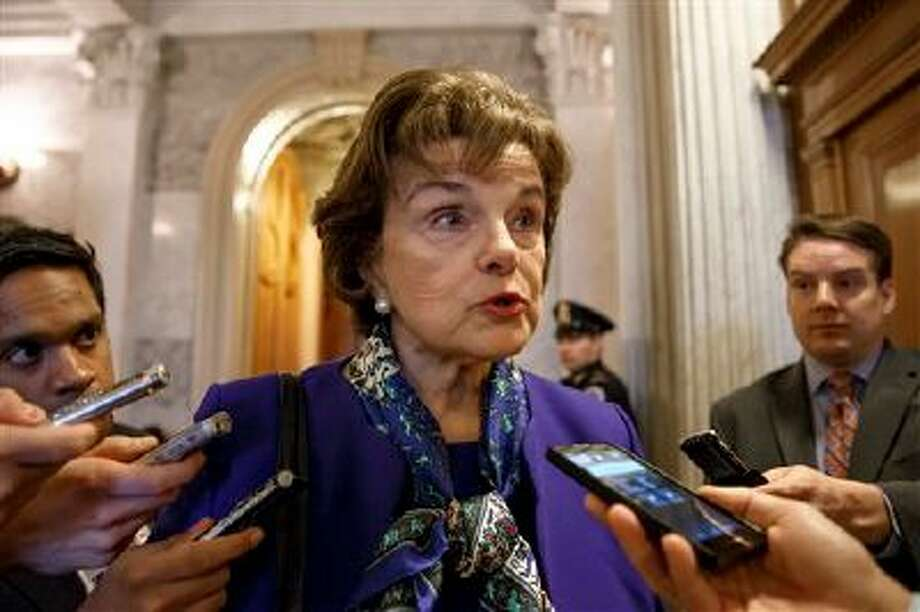 Senate Intelligence Committee Chair Sen. Dianne Feinstein, D-Calif. talks to reporters as she leaves the Senate chamber on Capitol Hill in Washington, Tuesday, March 11, 2014, after saying that the CIA's improper search of a stand-alone computer network established for Congress has been referred to the Justice Department. The issue stems from the investigation into allegations of CIA abuse in a Bush-era detention and interrogation program. (AP Photo/J. Scott Applewhite) Photo: ASSOCIATED PRESS / THE ASSOCIATED PRESS2014