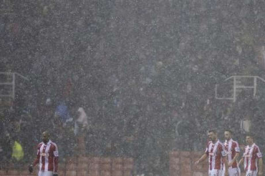 Stoke players walk from the pitch as hail falls during their team's English League Cup quarter-final soccer match against against Manchester United at the Britannia Stadium, Stoke, England, Wednesday Dec. 18, 2013.