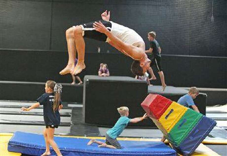 In this Wednesday, July 31, 2013 photo, Jacob Terrell, of Pleasantville, flips as others play at the Get Air Hang Time indoor trampoline park in Orem, Utah. Indoor trampoline parks have cropped up around the country in recent years, offering customers a chance to bounce, flip and jump in wall-to-wall trampolines. The jump gyms offer the kind of rain-or-shine suburban entertainment popular for birthday parties and summer camps. But some doctors and officials say the parks are dangerous and can cause serious injuries. (AP Photo/Rick Bowmer) Photo: AP / AP