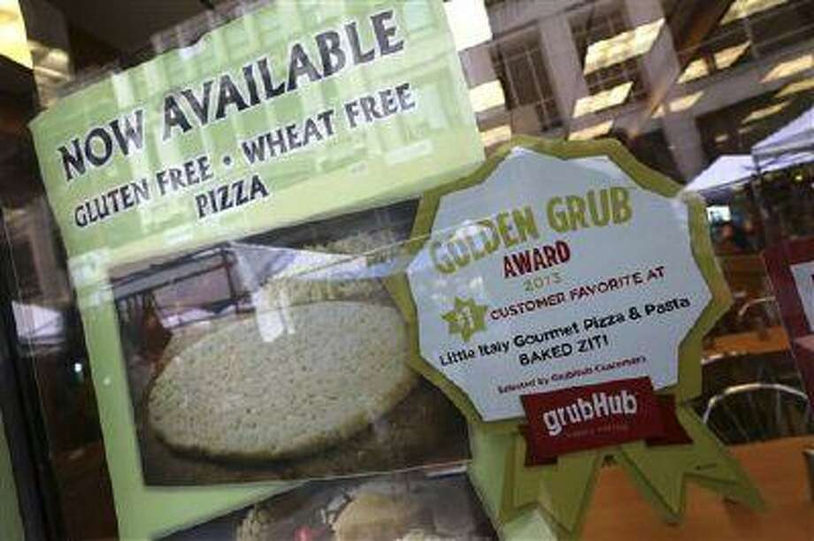 A GrubHub sticker is displayed next to photographs of items on the menu in the window of a restaurant in New York's Times Square, Saturday, Aug. 10, 2013. Rivals Seamless and GrubHub said Friday that they have completed their combination, creating an online takeout company covering about 25,000 restaurants in 500 cities. (AP Photo/Mary Altaffer) Photo: AP / AP