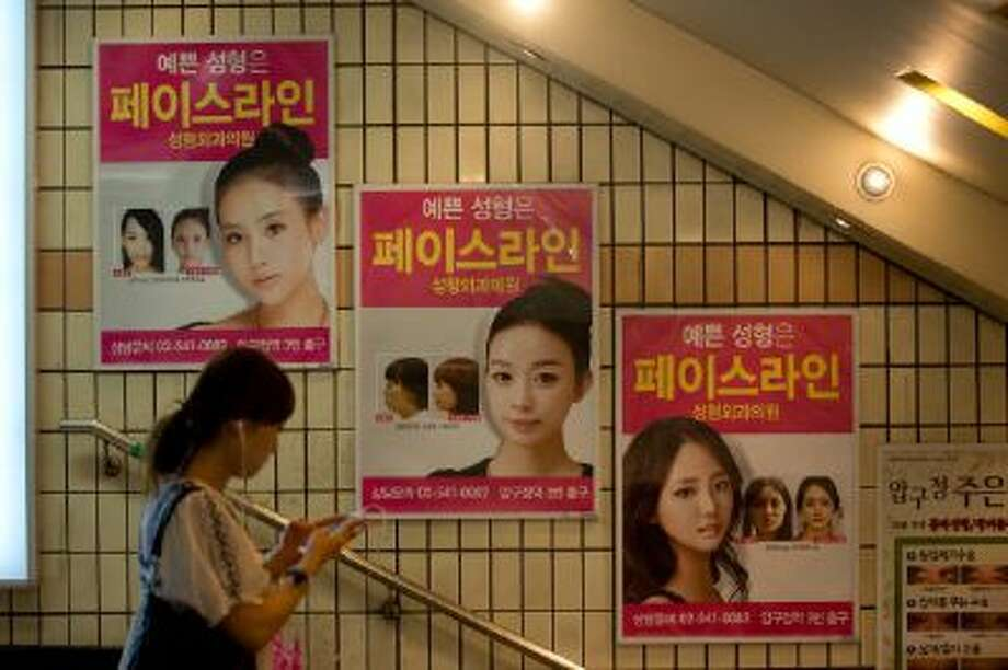 Advertisements for plastic surgery clinics are displayed in July at a subway station in Seoul. Photo: AFP/Getty Images / 2013 AFP