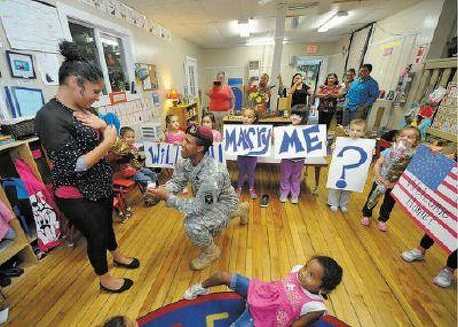 Anthony Figueroa, 20, of Fitchburg, who is in the Army stationed at Fort Bragg, N.C., surprises his girlfriend, Lauren Quintero, 18, of Leominster, by proposing to her Friday at her workplace, the Busy Bees Preschool in Fitchburg. Her answer? Yes, of course.