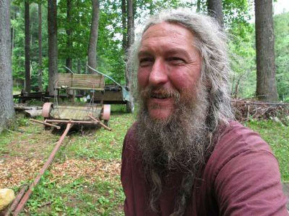 Eustace Conway sits near horse-drawn farm implements at his Turtle Island Preserve in Triplett, N.C., on Thursday, June 27, 2013. People come from all over the world to learn natural living and how to go off-grid, but local officials ordered the place closed over health and safety concerns.